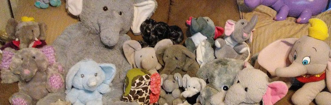 A collection of stuffed elephants of varying colors and sizes